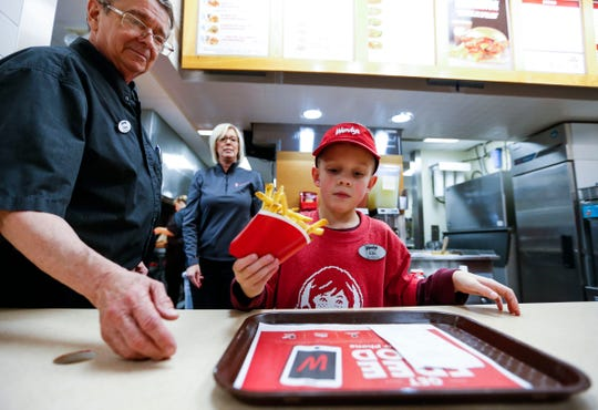 Seven-year-old Eric Johnson places fries onto a tray at Wendy's on South Campbell Avenue under the supervision of General Manager Glenn Schonder on Monday, Nov. 11, 2019. Johnson, who was diagnosed with autism at the age of 3, told his mom that he wanted to be a manager at Wendy's for Career Day at school, and she worked with the local franchise to make it happen.
