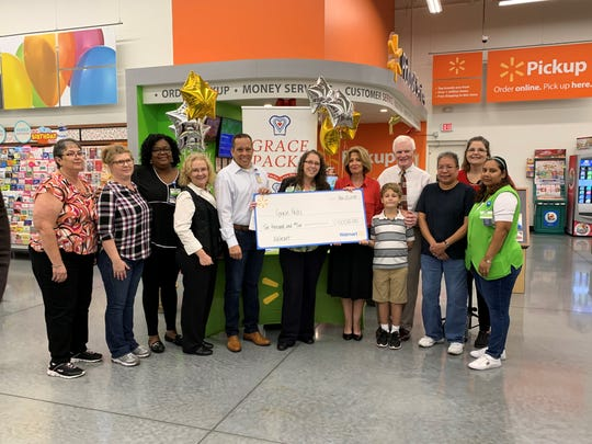 Walmart store manager Heather Gunnell and Grace Packs founder Laura Klosterman were presented a check for $10,000 after being one of 25 winners of the Walmart Associate Challenge.