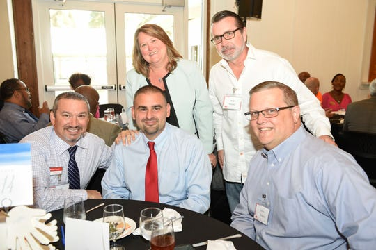 Michael Hayban, seated, from left, Jason Zigrand and Louis Androvic, with Cherise Westenberger, standing, and Rob Troupe at the Hand Up Luncheon for United Against Poverty St. Lucie County at Riverwalk in Fort Pierce on Oct. 24, 2019.