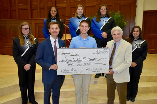 The Indian River Symphonic Association recently presented the Sebastian River High School Band with $2,000. Pictured are, from left, front row, Sarah Cosner, association Treasurer Dave Johnson, SRHS Director of Bands Chase Jones, assocation Vice President Ed Shanaphy, and Hannah Flood, with Marissa Gordian, back row, Rian Butler and Emily Chester.