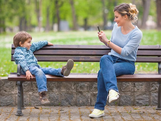 A young mother photographing her son posing on a park bench.