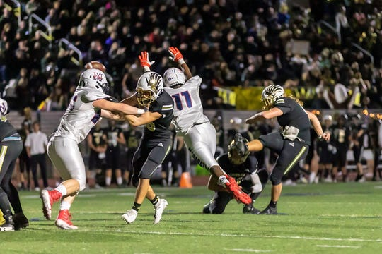 Gianni Smith kicks an extra point during unbeaten Oak Park's first-round playoff win on Nov. 8. While Smith has starred at quarterback in his senior season, his future may be as a placekicker in college.