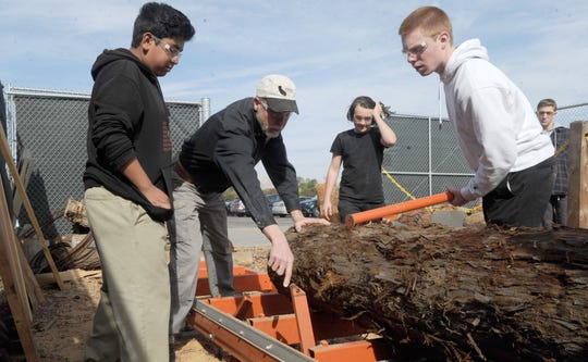 Royal High freshman Sam Molina, from left, woodshop teacher David Sorenson, freshman Aiden Stoner and senior Heith Parker help align a redwood log before milling. The Royal High students along with counterparts from Simi Valley High are helping to recreate two wooden finials on two historic Simi Valley homes.
