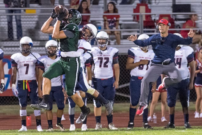 Tulare Western Coach Ryan Rocha, right, leaps with his defender Isaiah Gomez as El Diamante's Cameron Beans brings a pass from Parker Boswell in a non-league high school football game at Groppetti Automotive Visalia Community Stadium on Friday, August 17, 2018.