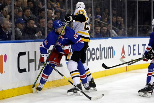 Nov 12, 2019; New York, NY, USA; New York Rangers defenseman Ryan Lindgren (55) and Pittsburgh Penguins center Nick Bjugstad (27) battle for the puck during the first period at Madison Square Garden.