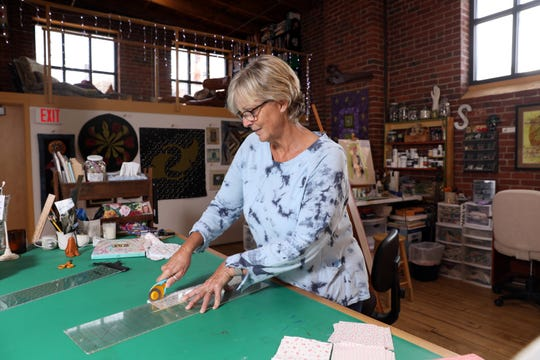 Susan Nash, a part owner of The Art Loft in downtown Zanesville, works on a piece. She specializes in mixed-media art quilts, often reflecting on nature.