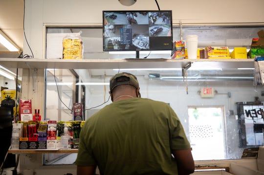 Shantez Rias stands beneath a surveillance camera display at Chalie's Convenient Market in Washington Park, Ill.