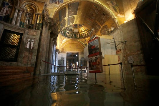 The entrance to St. Mark's Basilica is flooded on the occasion of a high tide, in Venice, Italy, Tuesday, Nov. 12, 2019.