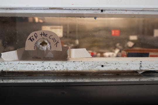 """At Chalie's Convenient Market, the windows between the store owners and customers have bullet holes in them. Customers use one of the holes to slide in change under a handwritten sign, """"Tip the Cook."""""""