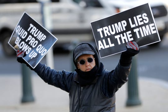 A protester holds signs outside the first public impeachment hearings of President Donald Trump's efforts to tie U.S. aid for Ukraine to investigations of his political opponents.