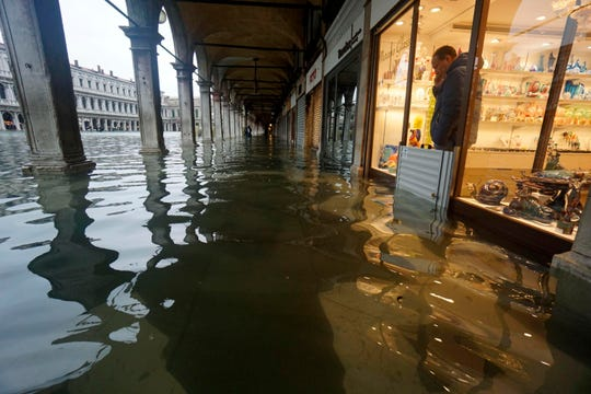 A shopkeeper looks out at the rising waters in St. Mark's Square during a high tide, in Venice, Italy.