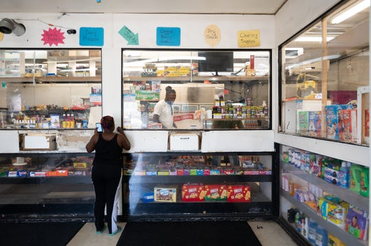 A woman places an order at Chalie's Convenient Market in Washington Park, Ill. The store is about 10 minutes outside St. Louis.