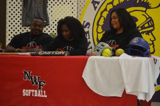 Alexandria Senior High's Cameron Hall (center) signs with Northwest Florida State College Wednesday.