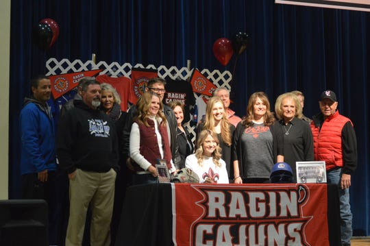 LaSalle softball player Taylor Snow (center) celebrates with friends and family after signing to UL Lafayette in November.