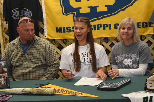 Aundria Eirls (center), of Rapides High School, reacts after signing to play with Mississippi College on National Signing Day, Nov. 13, 2019. With Aundria are her parents Jeremy Eirls and Christy Lemoine.