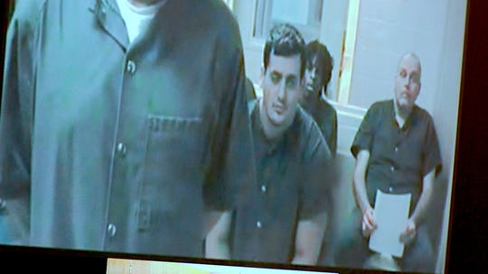 John Ozbilgen (center), who is charged with child pornography and linked to the missing Freehold woman, makes his first appearance Thursday, November 14, 2019, via video from the Monmouth County Jail.