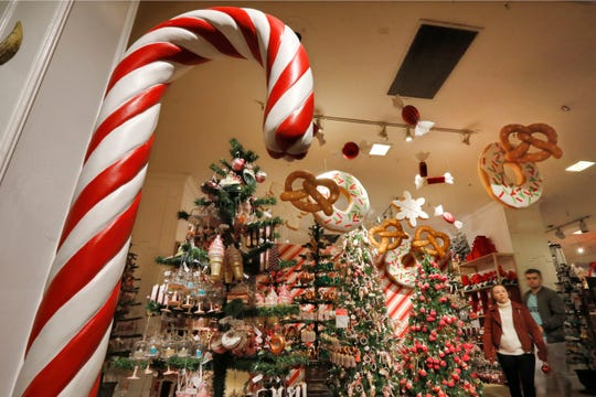 In this Tuesday, Nov. 5, 2019, photo shoppers browse the food-themed decorations in the Holiday Lane section at the Macy's flagship store, in New York. With three weeks until the official start of the holiday shopping season, the nation's retailers are gearing up for what will be another competitive shopping period. (AP Photo/Richard Drew)