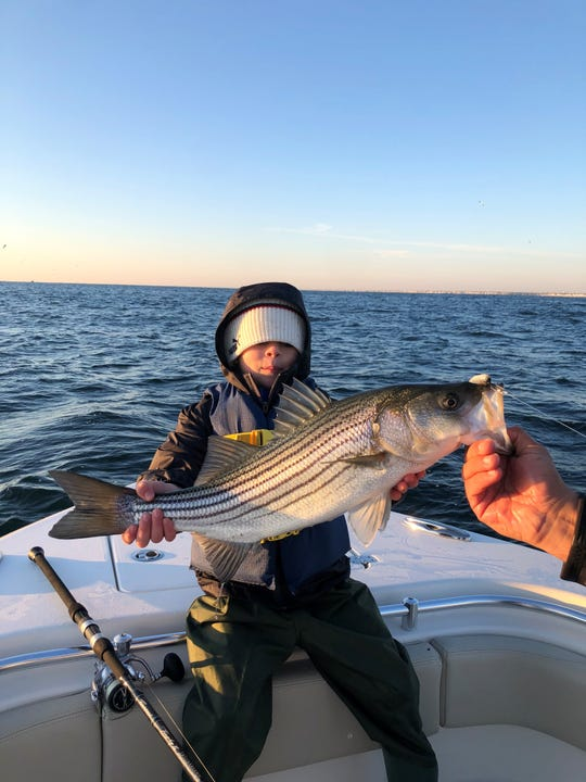 AJ Whiting, 7 of Brielle, with his first striped bass.
