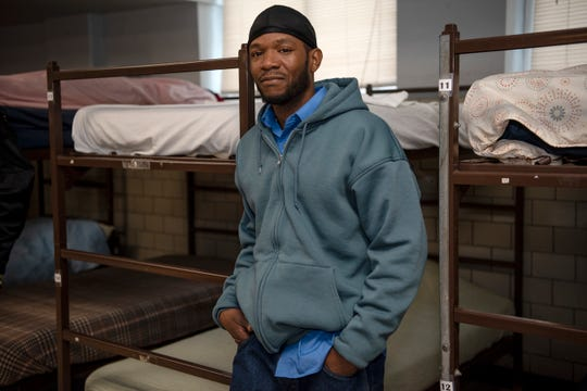Shawn Jackson, 43, poses for a portrait near his bed on Thursday, Nov. 14, 2019 at Haven of Rest Ministries in Battle Creek, Mich. Jackson is currently employed and is struggling to find affordable housing because of the felony charge on his record.
