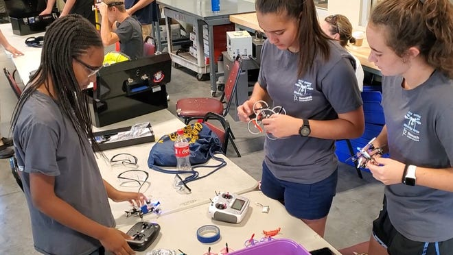 "The West Shore Jr/Sr High School ""Whirly Girls"" drone racing club make adjustments to their drones before a meet."