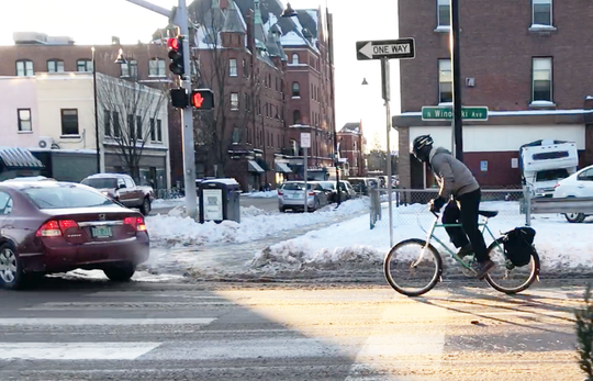 A cyclist enters the intersection of Pearl Street and Winooski Avenue on Nov. 13, 2019. This part of Winooski Avenue is generally considered unsafe for bicycle traffic.