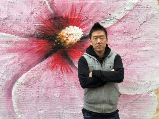 """Kil Lee, 35, of Corpus Christi, stands in front of """"The Dokyo Wall"""" mural at 424 N. Chaparral St. Lee plans to open a sushi restaurant in December or January called Dokyo Dauntaun in the building."""