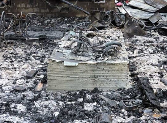 "This photo shows the bicycle of 5-year-old Aleigha Hayes among the wreckage of a fire that claimed her life in May of 2016. The photo, released by Vinton County Prosecutor Trecia Kimes-Brown, has ""haunted me since the day I first saw it"" and she is hoping it will help bring those with information about the fire forward with that information."