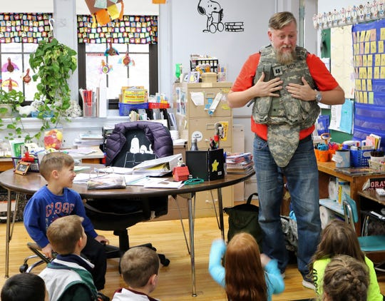 Anthony DeFoe, a 12-year veteran of the U.S. Army, speaks to first graders at McKinley School on Monday, Nov. 11, as his son, Quinn (left) proudly looks on.