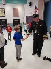 Commander Scott Scammel shaking hands with Holland Brook School student, Charlie Staudt.