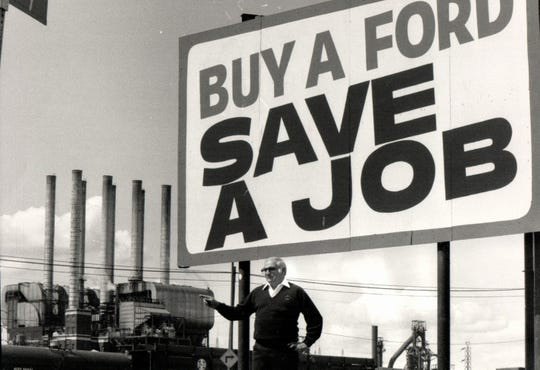 Mike Rinaldi, then president of UAW Local 600, stands at the sign in front of Dix headquarters and points to the Ford Rouge facility in 1983.
