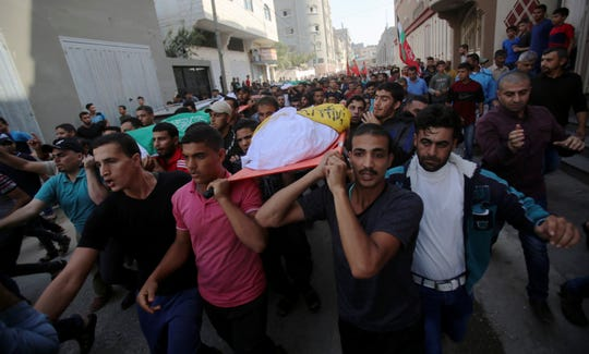 Mourners carry the bodies of Rafat Ayyad and his children, Islam and Amie, who were killed in an Israeli airstrike, during their funeral in Gaza City, Wednesday, Nov. 13, 2019.