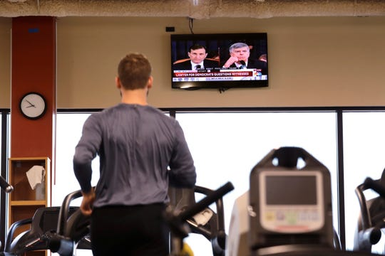 A gym club member runs on a treadmill and watches the public hearing of Donald Trump's impeachment investigation on a television Wednesday, Nov. 13, 2019, in Seattle.
