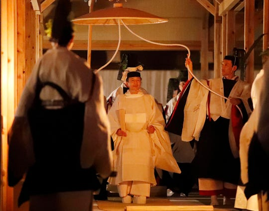 Japan's Emperor Naruhito, center, walks toward Yukiden, one of two main halls of the shrine for Daijosai, or great thanksgiving festival, at the Imperial Palace in Tokyo on Thursday.