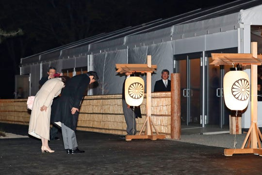 Japanese Prime Minister Shinzo Abe and his wife Akie Abe bow in front of the main gate of Daijo hall to attend a ceremony for Emperor Naruhito in Tokyo on Thursday.