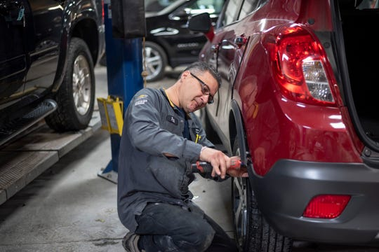 Auto body technician Pete Tzianis replaces the rear bumper on a Buick Encore at the Matthew Hargreaves Chevrolet dealership in Royal Oak.