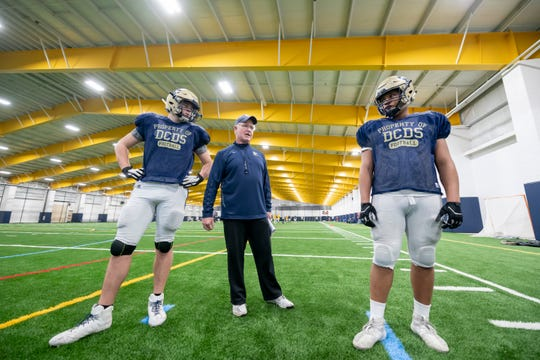 Country Day head coach Dan MacLean, center, goes through plays with offensive linemen Caleb Tiernan, left, and Will Leggon.