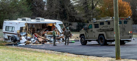 Police examine a stolen RV after ramming it multiple times with an armored vehicle, right, while searching for a Marine deserter who is wanted for questioning in a murder case, in Roanoke, Va.