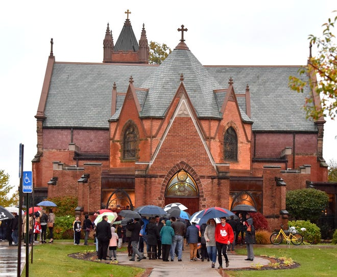 Mourners gather at St. Paul on The Lake in Grosse Pointe Farms on Oct. 30 to remember Briggs and Logan Connolly who died in a house fire. Many wore hockey jerseys to remember the young boys, who were avid hockey players.