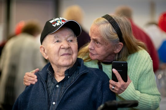 Army veteran Henry Kroll, left, is given congratulations from family friend Roberta Kordish after receiving three medals from his time in World War II.