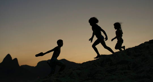 In this Aug. 1, 2016 file photo, children are silhouetted against the setting sun as they run on the sand at Ipanema beach in Rio de Janeiro, Brazil. Homeland Security investigators who uncover child exploitation initiated more than 4,000 cases around the world in 2019. Data obtained by The Associated Press shows the investigations resulted in thousands of arrests and the identification of more than 1,000 victims.