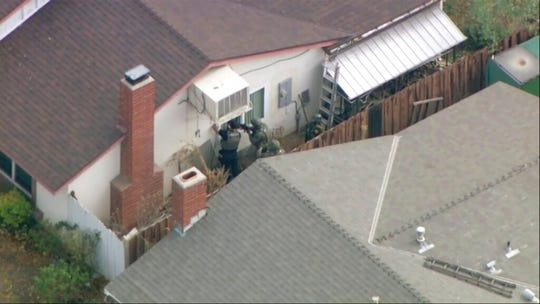 Police search a home in connection with shooting at Saugus High School on Thursday, Nov. 14, 2019 in Santa Clarita, Calif. Los Angeles County Sheriff Alex Villanueva tweeted that the suspect was in custody and was being treated at a hospital. He said the suspect was a student but gave no further information.