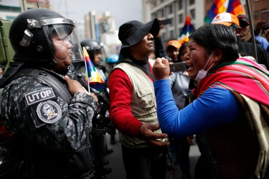 A supporter of Bolivia's former President Evo Morales yells at a police officer, telling him to respect the nation's indigenous people in La Paz, Bolivia, Tuesday, Nov. 12, 2019.