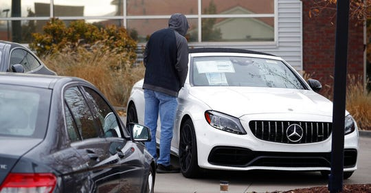 In this Sunday, Oct. 20, 2019, file photo, a prospective buyer looks over an unsold 2019 AMG C63 cabriolet at a Mercedes Benz dealership in Littleton, Colo. A measure of U.S. consumer sentiment posted its steepest three-week slump since 2008 as optimism tumbled among lower-income Americans.