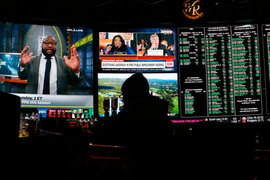 The first public impeachment hearing of President Donald Trump plays on a screen at the Superbook sports book inside the Westgate casino-hotel Wednesday, Nov. 13, 2019, in Las Vegas.