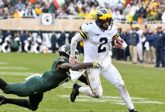 Michigan quarterback Shea Patterson picks up a first down and is taken down by MSU's David Dowell during last year's game in East Lansing.
