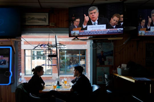 Olivia Tobin and her fiance, Jordan Ashby, ignore the televised impeachment hearings playing on monitors at the Commercial Street Pub, Wednesday, Nov. 13, 2019, in Portland, Maine.