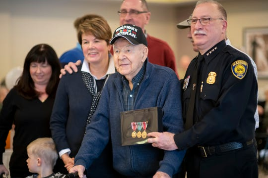 Army veteran Henry Kroll poses for a photo with Dearborn Police Chief Ronald Haddad after receiving three medals from his time in World War II.