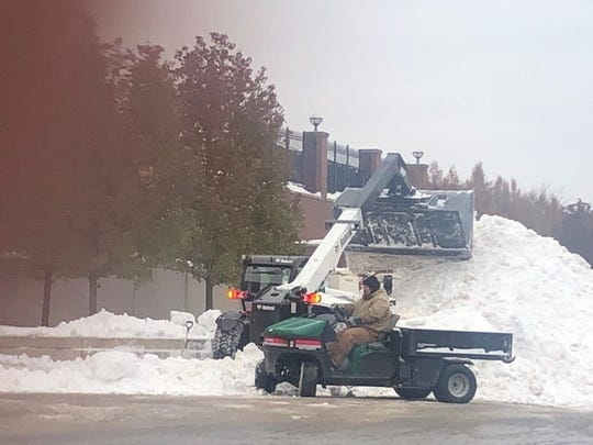 Workers remove snow from Michigan Stadium on Thursday.