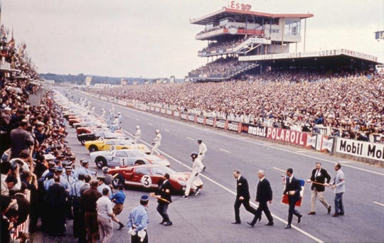 The start of the 1966 24 Hour of Le Mans. Having waved the starting flag, Henry Ford II (first suit on the left) hustles across the track while the drivers spring to their cars.