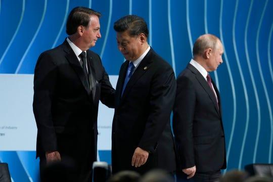 Brazil's President Jair Bolsonaro, left, greets China's President Xi Jinping, center, next to Russia's President Vladimir Putin, during the BRICS Business Council prior the 11th edition of the BRICS Summit, in Brasilia, Brazil, Wednesday, Nov. 13, 2019.